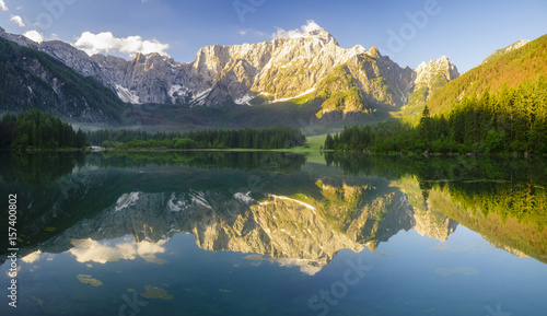 Poster Printemps Panoramic view of beautiful white winter wonderland scenery in the Alps with mountain summits reflecting in crystal clear mountain lake on a colorful dawn