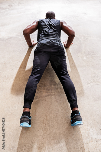 Serious sportsman making bodybuilding exercises Poster