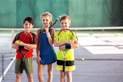 Girl and boys playing tennis with enjoyment