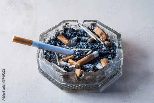 A cigarette with a filter in a dirty ashtray with cigarette butts, conceptual ph Wallpaper Mural