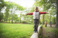 Little Boy Walking On A Log In...