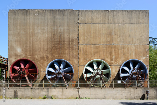 Photo  Industrial rusty ventilators in vintage colors red, blue, green at Landschaftspa
