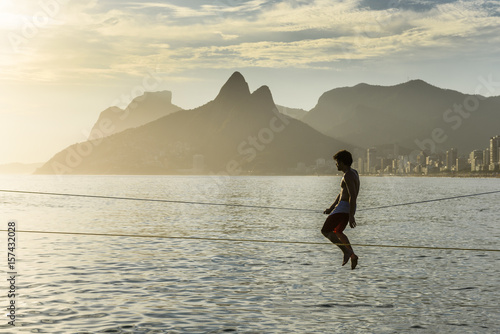 Beach A Man Sitting On A Slackline At Arpoador Beach During The Sunset, Rio De Janeiro, Brazil