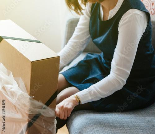 Plakat Młoda piękna kobieta na salonie sofa, gdy rozpakowuje unbox duże pudełko kartonowe zawierające nowe piękne ubrania