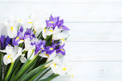 Bouquet of iris flowers on white wooden table