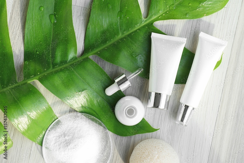 Fototapety, obrazy: Cosmetic bottle containers with green herbal leaves, Blank label for branding mock-up, Natural beauty product concept. (Color Processed)