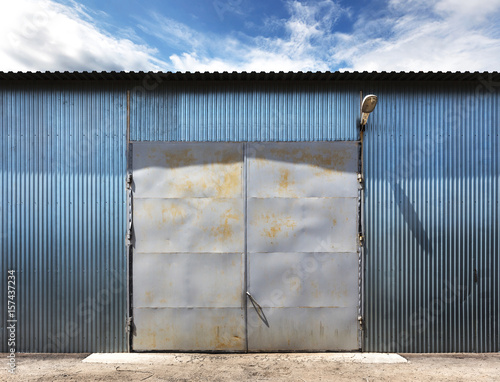Staande foto Industrial geb. Photo of old grunge closed warehouse, blue sky on background