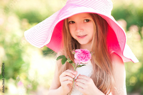 b4957b178b0 Smiling cute baby girl 4-5 year old holding flower wearing big hat in meadow