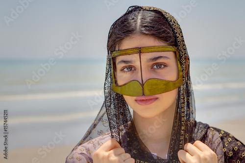 Photo  Girl in mask bandari woman, beach of Persian Gulf, Iran.