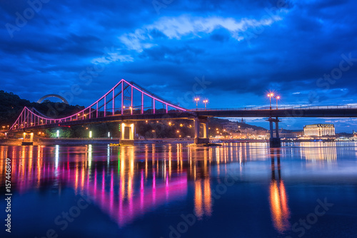 In de dag Havana Night european city in colorful lights and reflection in water, Kyiv (Kiev) the capital of Ukraine. Pedestrian bridge across the Dnieper river and view to the river station