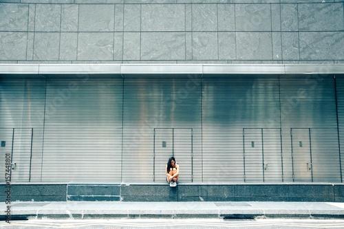 Sad Woman Sitting Against Building