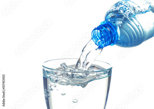 Papiers peints Eau Water pouring from bottle into glass on white background
