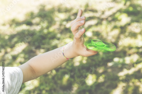Fotografie, Obraz  Child playing with a green hand spinner fidget toy