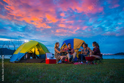 Poster Camping Camping of happy asian young travellers at lake, asian man and women group, relaxing, sing a song and cooking, at sunset.