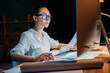 young concentrated asian businesswoman in eyeglasses working with documents and computer