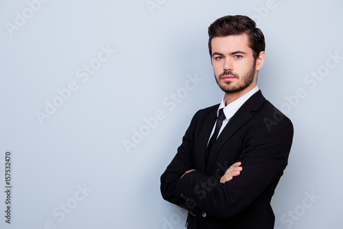 Valokuva  Young confident man in black suit with crossed hands standing half-turned agains