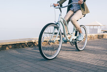 Woman Is Riding A Beautiful Bicycle Along The Sea