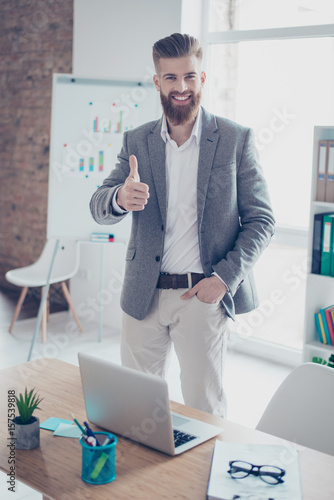 Fotografía  Successful young man is showing thumb up in office