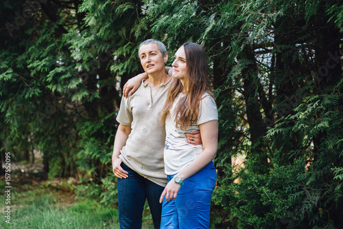 Fotografia  Smiling middle-aged mother and adult daughter in law hugging before the green trees in yard