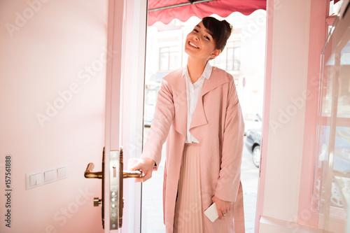 Fotografía  Smiling girl in pink coat entering cafeteria