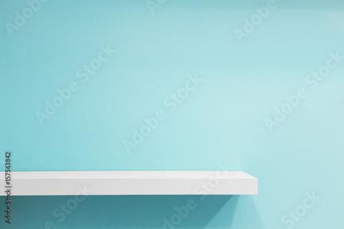 Empty white shop shelf, retail shelf on blue vintage background. Wallpaper Mural