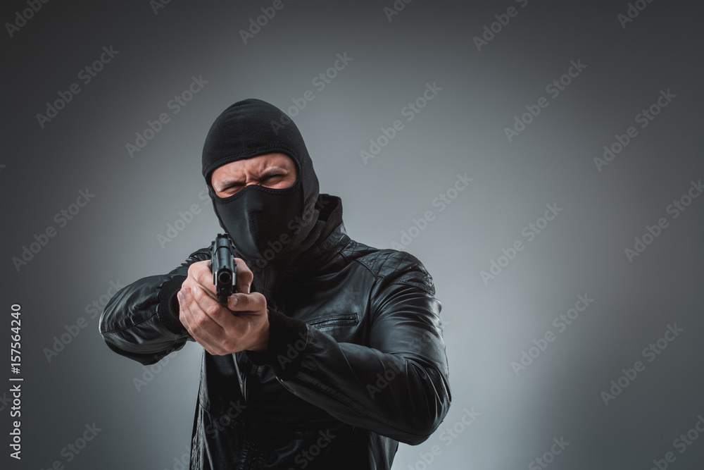 Fototapeta Robber with a gun, studio shot