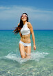 happy beautiful girl with fitness body running in sea water