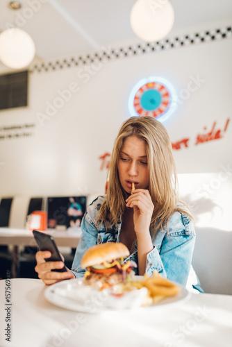 Tuinposter Kruidenierswinkel Young woman eating burger in restaurant