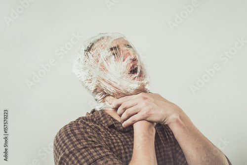 Photo Suicide Young Man in Plastic Wrap Strangling Yourself With Your Hands