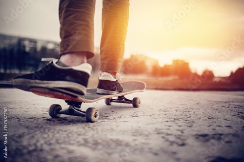 A boot of a skateboarder's shoes is standing on a skateboard ride in the sunset on the road, close-up. Concept street sports in leaky boots