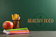 Apple and school stationery on table. Text HEALTHY FOOD on chalkboard