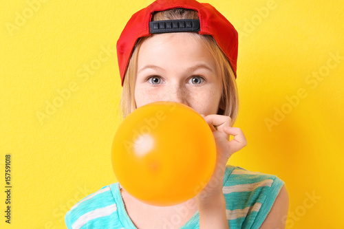 фотография Funny teenager girl in red hat inflating balloon on yellow background