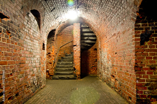 Fotografie, Obraz  Arched corridor of the old Prussian fortress of red brick, ending with a spiral