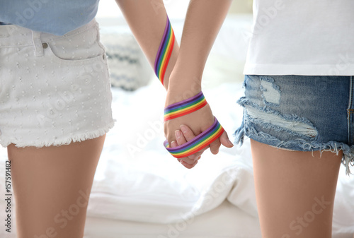 Leinwand Poster Young lesbian couple holding hands with rainbow ribbon, closeup