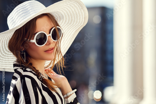 64ba51fe571 Outdoor close up portrait of young beautiful girl posing in street. Model  wearing stylish round sunglasses