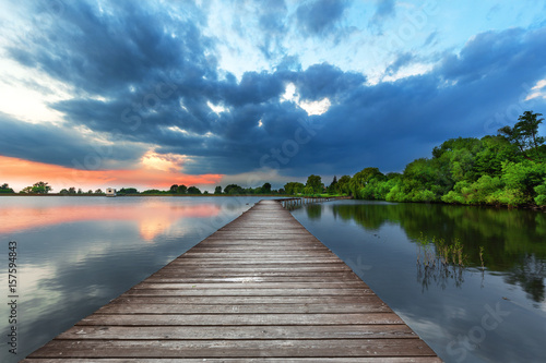 Fototapeta Wooden path bridge over lake at stormy sunset