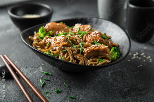 asian soba noodle and teriyaki salmon  in black bowl
