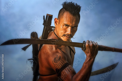 Leinwand Poster Ancient warrior man of soldier of Bang Rachan District Thailand hold sword fight,Images of dirty middle-aged fighters and swords