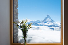 Scenic View On Snowy Matterhorn Peak In Sunny Day With Blue Sky And Blur Window In Foreground, Switzerland.