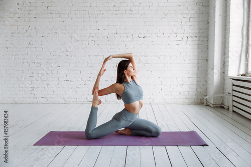 Young girl doing yoga in the room