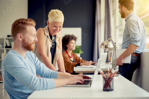 Fototapety, obrazy: Caucasian businesswoman giving advice to her colleague while standing in modern office