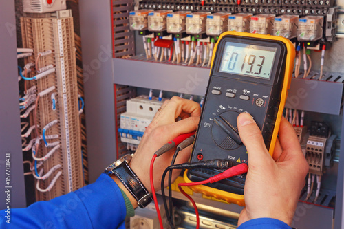Fotografie, Obraz  Multimeter in the hands of an electrician close-up on a blurred background of el