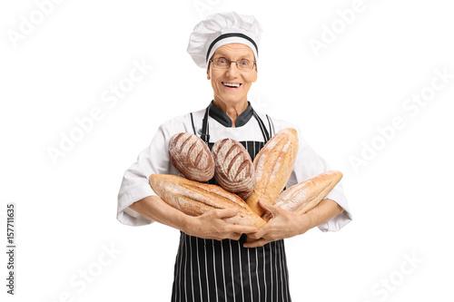 Elderly baker holding loaves of bread Fototapeta