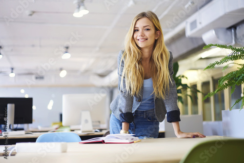 Pinturas sobre lienzo  Cheerful blonde young female student of IT school preparing for quiz reading not