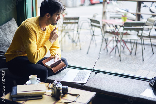 Valokuva  Thoughtful creative writer looking out window of coffee shop sitting inside in f