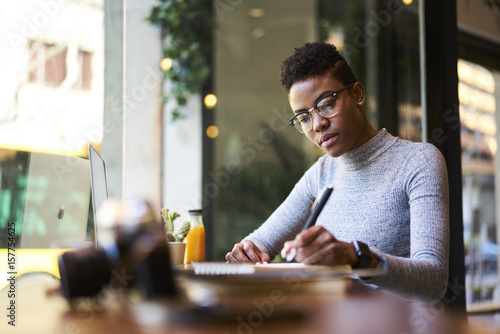 Photo  Concentrated afro american experienced woman journalist in glasses creating arti