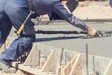 Construction Worker Leveling Concrete Pavement Outdoors.