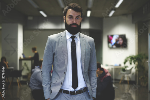 Fotografía  Half length portrait of handsome bearded CEO of IT corporation standing on worki