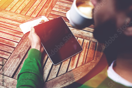 Deurstickers Ontspanning Rear view of young male freelancer drinking hot coffee and working on digital tablet in cafe outdoors, smart business man reading last news or electronic book touch pad with copy space screen for