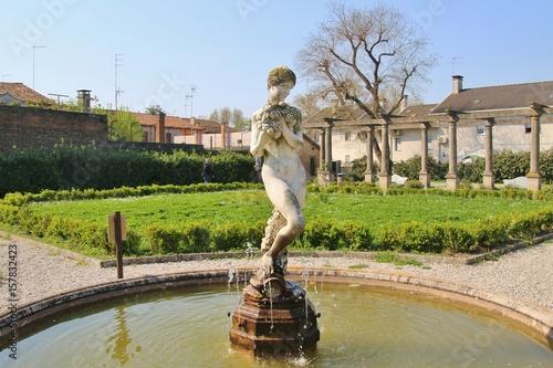 Photo In the town Adria, Italy: The public park Giardini Scarpari, statue of a woman with vines in the center